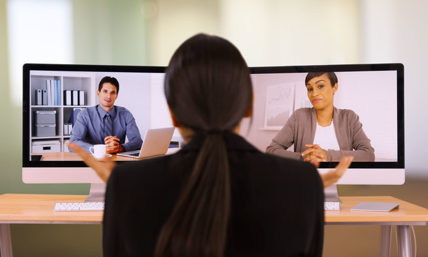 A young businesswoman video chats with her co-workers.