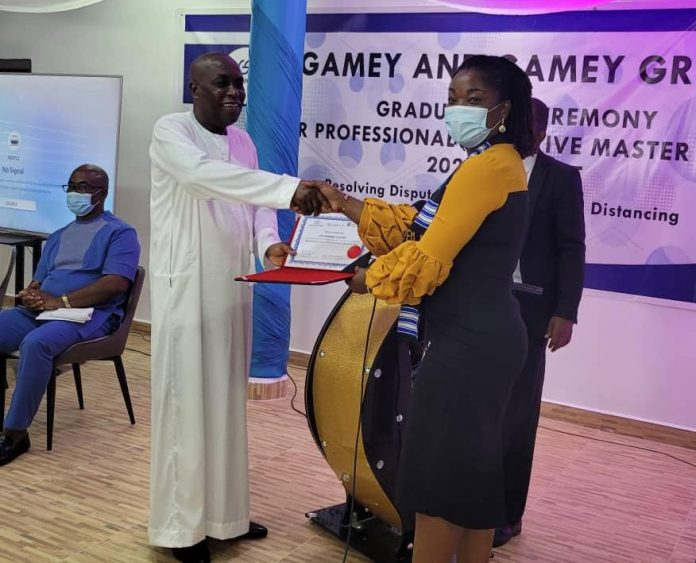 Mr Gamey presenting a certificate to Mrs Vida Essiaw Malik of Consolidated Bank Ghana