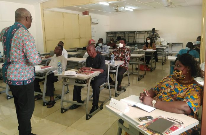 Mr_George_Agbozo_left_interacting_with_the_participants-scaled.jpg